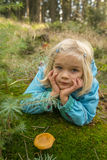 Cute little girl picking mushrooms in summer forest Stock Image