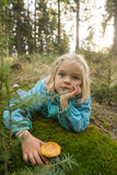 Cute little girl picking mushrooms in summer forest Stock Images