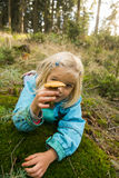 Cute little girl picking mushrooms in summer forest Stock Photos