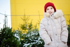 Cute little girl picking a tree at Christmas tree market on chilly winter day. Choosing Xmas tree for family celebration at home. Wonderful Christmas time stock photography
