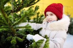 Cute little girl picking a tree at Christmas tree market on chilly winter day. Choosing Xmas tree for family celebration at home. Wonderful Christmas time stock photo
