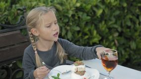 Cute little girl with pigtails eating dessert stock footage