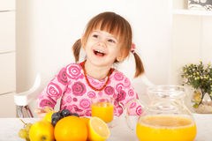 Cute little girl with pigtails sitting and laughing Royalty Free Stock Images