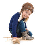 Cute little girl in pilot hat with wooden plane Royalty Free Stock Images