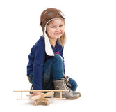 Cute little girl in pilot hat with wooden plane Stock Image