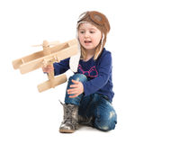 Cute little girl in pilot hat with wooden plane Royalty Free Stock Photography