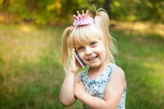 Cute little girl with pink crown talk by phone. And smile, outdoors with copy spase Royalty Free Stock Image