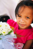 Cute little girl in pink dress holding white flowers bouquet on wedding celebration. Little flower girl at wedding Royalty Free Stock Photo