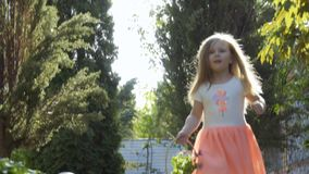 Cute little girl in pink dress run among green trees in the garden. Beautiful little girl in lovely dress run on the path among trees in the garden with basket stock video footage