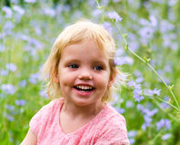 Cute little girl in a pink dress smiling in park Royalty Free Stock Photography
