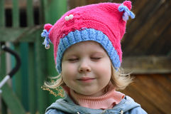 Cute little girl in a pink hat. He closed his eyes stock photography