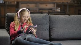 Cute girl in headphones using touchpad on sofa. Cute little girl in pink headphones and eyeglasses sitting on the sofa and using digital tablet pc. Blond teenage stock footage