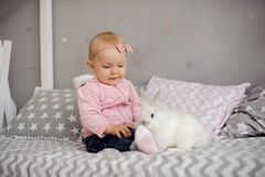 Cute little girl playing with white rabbit stock photography