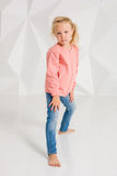 Cute little girl in pink jacket and jeans on white background Stock Photos