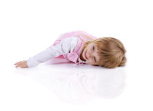 Cute little girl in a pink lie on the floor. Studio shot stock photo