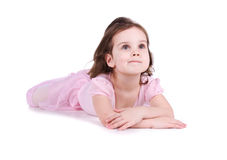Cute little girl in a pink lie on the floor. Studio shot stock photography