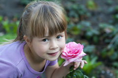 Cute little girl with pink rose flower Stock Photos