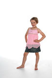 Cute little girl in pink shirt. And denim skirt with her hands on her hips Stock Photo