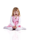 Cute little girl in a pink sit cross-legged Royalty Free Stock Photo
