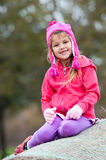 Cute little girl in pink sitting on hay bale. Royalty Free Stock Image