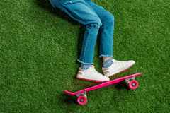 Cute little girl with pink skateboard lying on green lawn Stock Images