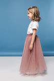 Cute little girl in pink skirt smiling and looking away Royalty Free Stock Image