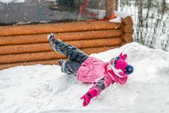 Cute little girl in pink sport suit having fun playing outdoors during snowfall in winter. Children winter seasonal outdoor. Activities stock image