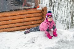 Cute little girl in pink sport suit having fun playing outdoors during snowfall in winter. Children winter seasonal outdoor. Activities stock photos