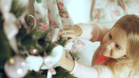 Cute little girl in a pink sweater decorates a Christmas tree Royalty Free Stock Image