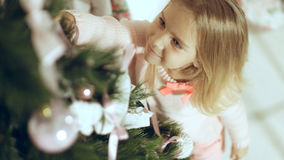 Cute little girl in a pink sweater decorates a Christmas tree Royalty Free Stock Photo