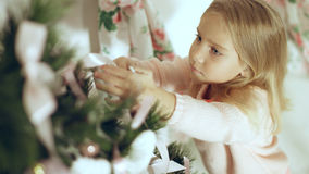 Cute little girl in a pink sweater decorates a Christmas tree Stock Photography