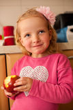 Cute little girl in pink sweater eats apple in the kitchen Stock Images