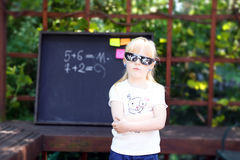 Cute little girl with pixel glasses  standing ahead  blackboard Stock Images