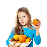 Cute little girl with plate of fruits: kiwi, date plum, mandarin Royalty Free Stock Images