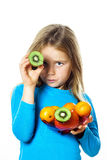 Cute little girl with plate of fruits: kiwi, date plum, mandarin Royalty Free Stock Image