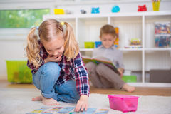 Cute little girl play game, boy read book. Cute little girl play board game, boy read book Royalty Free Stock Images