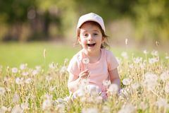 Cute little girl play in the park. Beauty nature scene. With colorful background at summer or spring season. Family outdoor lifestyle. Happy girl relax on green Stock Image