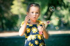Cute little girl play in park blow soap bubbles. Front view summer day Stock Photos