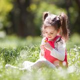 Cute little girl play in the park with flowers. Beauty nature scene with colorful background at summer or spring season. Family. Outdoor lifestyle. Happy girl stock image