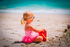Cute little girl play with sand on beach. Vacation royalty free stock photography