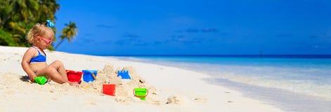 Cute little girl play with sand on the beach Stock Photos