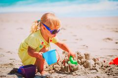 Cute little girl play with sand on beach. Vacation royalty free stock photo