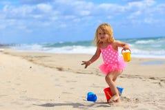 Cute little girl play with sand on beach. Cute little girl play with sand and water on beach Stock Photo