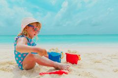 Cute little girl play with sand and toys on beach. Vacation stock images