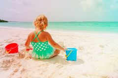 Cute little girl play with sand on beach. Cute little girl play with sand on tropical beach Royalty Free Stock Photo