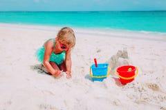 Cute little girl play with sand on beach. Cute little girl play with sand on tropical beach Royalty Free Stock Photos
