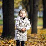 Cute little girl on playground in autumnal park Stock Photo
