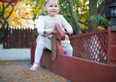 Cute little girl at playground. Cute little girl swinging at playground Royalty Free Stock Image