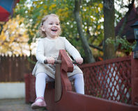 Cute little girl at playground. Cute little girl swinging at playground Stock Photo