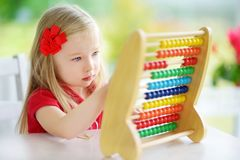 Cute little girl playing with abacus at home. Smart child learning to count. Cute little girl playing with wooden abacus at home. Smart child learning to count royalty free stock images